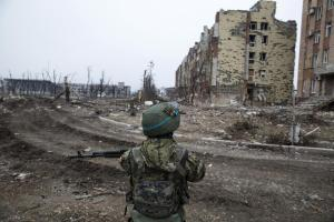An armed man with the separatist self-proclaimed Donetsk People's Republic army stands near a building damaged by months of fighting at the Donetsk airport