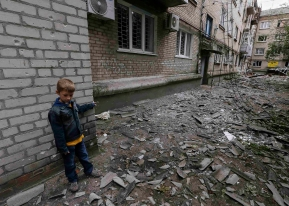A boy plays near a residential building, damaged by what locals say was overnight shelling by Ukrainian forces, in Slaviansk